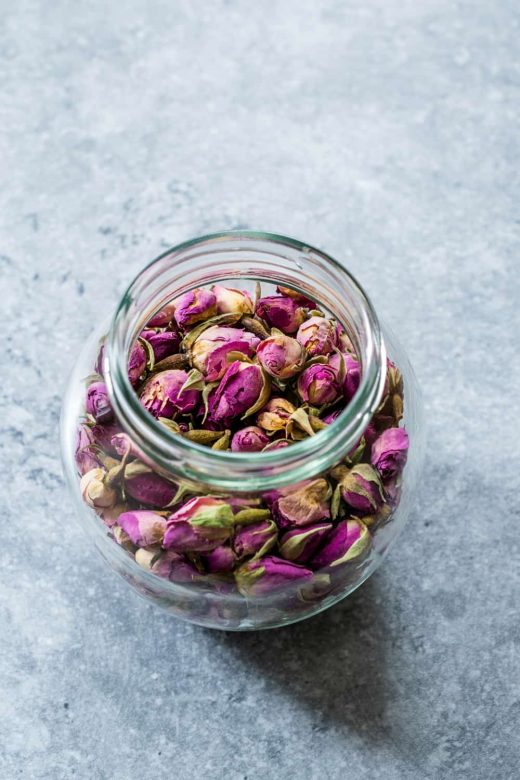 Rose petals in jar, an ingredient for homemade lip balm.